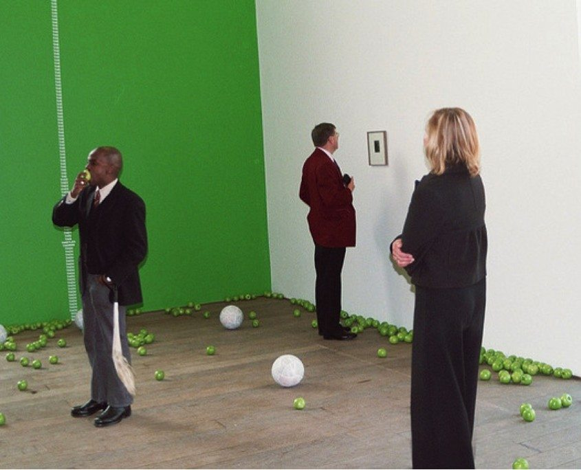 Fig. 2, Samson Kambalu (left) eating an apple and carrying a fly-whisk with patrons viewing (Bookworm) The Fall of Man (2003).